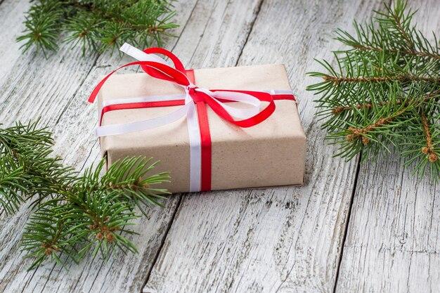 Natale con il regalo e l'albero di abete sulla tavola di legno bianca.