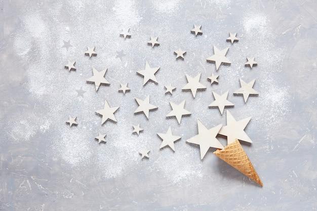 Natale con stelle di legno bianche nel cono di cialda cosparso di zucchero a velo. vista piana laici, primo piano, vista dall'alto sul tavolo di legno chiaro, posto per il vostro testo