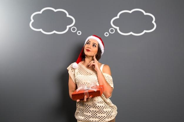 Natale donna cerca spazio vuoto copia tenere presente confezione regalo, giovane donna sorriso felice indossare cappello di babbo natale, attraente ragazza festa di capodanno, sulla lavagna con palloncini vuoti