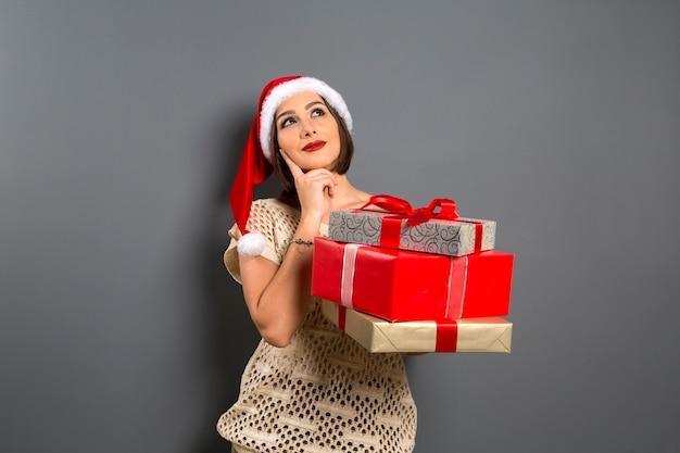 Natale donna cerca vuoto copia spazio tenere confezione regalo presente, giovane sorriso felice donna indossare cappello di babbo natale, attraente festa di capodanno ragazza,