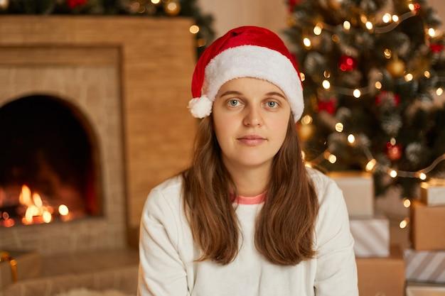 Donna di natale in cappello della santa che si siede nella decorazione del soggiorno vicino al camino e all'albero di abete