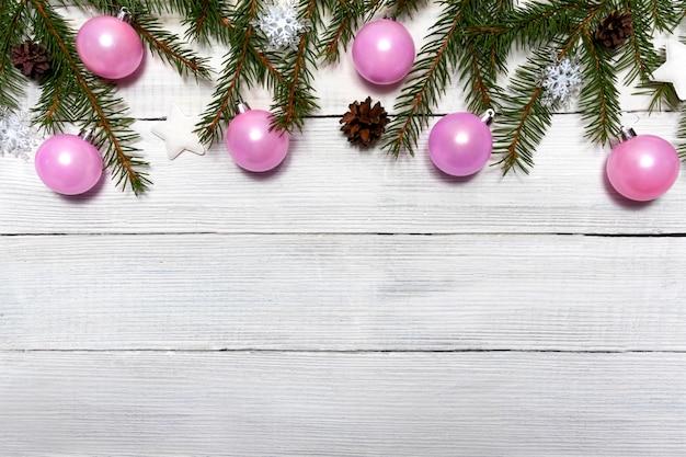 Fondo di legno di natale con palloncini rosa e abeti. decorazione di natale sulla tavola di legno bianca
