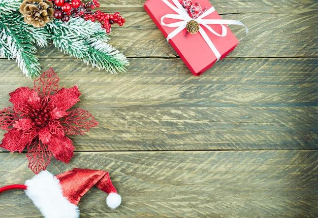 Fondo di legno di natale con ramo di abete e bacche, scatola rossa con un regalo, cappello della santa. una copia dello spazio.