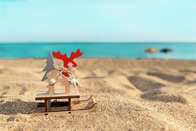 Renne di legno di decorazione in legno di natale su una slitta sulla spiaggia tropicale vicino all'oceano