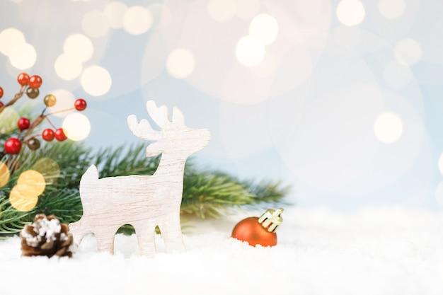 Natale cervo in legno nella neve con decorazioni di capodanno