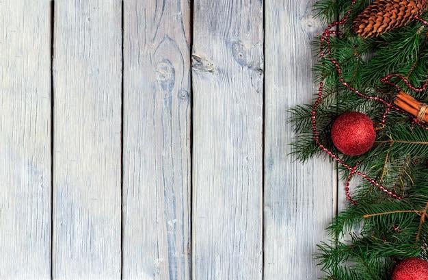 Sfondo chiaro di legno di natale con rami di abete e palle di natale