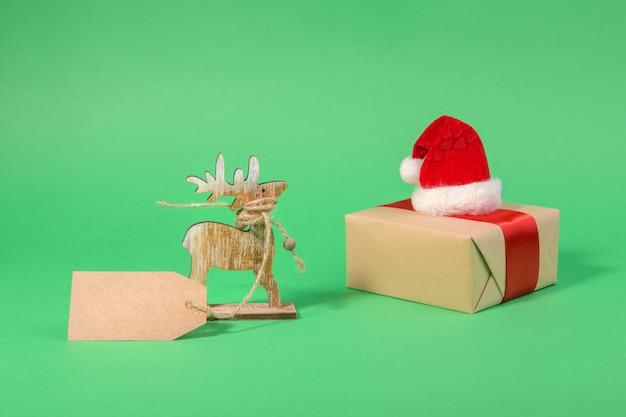 Natale renne in legno con tag regalo e confezione regalo con red santa hat su un verde con spazio copia, vendita di natale, concetto di festa