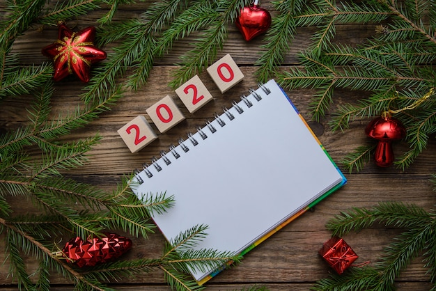 Tavolo in legno di natale con blocco note e ornamenti per il 2020 nuovo anno