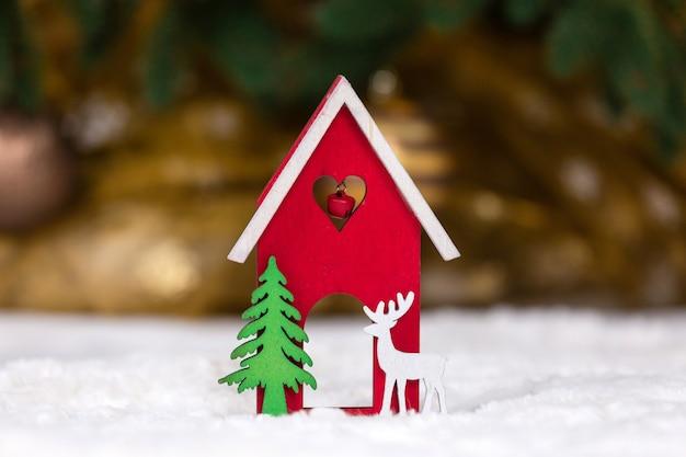 Casa del giocattolo di legno di natale, cervi e albero su una coperta bianca che imita la neve.