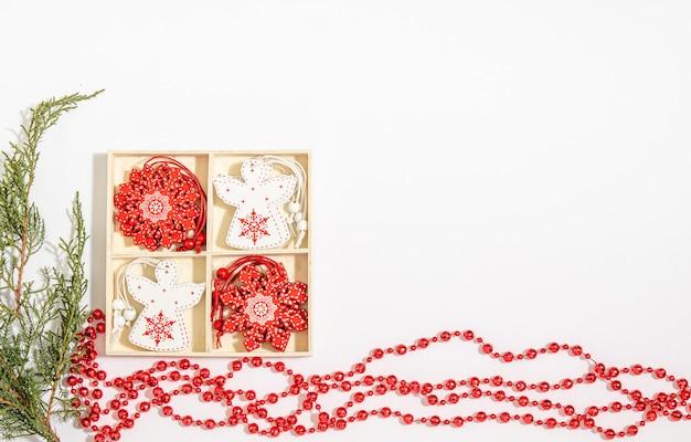 Giocattoli di legno di natale angelo bianco e fiocco di neve rosso in una scatola di legno, perline rosse, rami di ginepro su uno sfondo bianco.