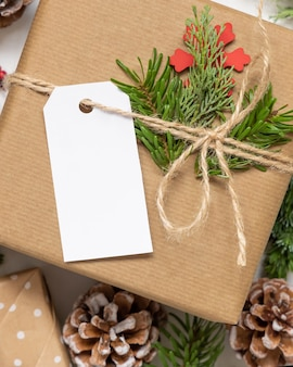 Regalo di natale avvolto con etichetta regalo di carta con rami di abete, pigne e decorazioni natalizie da vicino. composizione invernale rustica con etichetta regalo vuota mockup, spazio copia, disposizione piatta