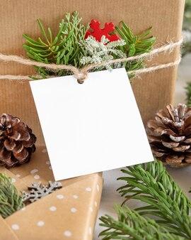 Regalo di natale avvolto con etichetta regalo di carta quadrata su un tavolo bianco con rami di abete e decorazioni da vicino. composizione invernale rustica con etichetta regalo vuota mockup, spazio copia