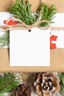 Regalo di natale avvolto con etichetta regalo di carta quadrata su un tavolo bianco con rami di abete e decorazioni vista dall'alto. composizione invernale rustica con etichetta regalo vuota mockup, copia spazio
