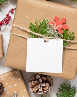 Regalo di natale avvolto con etichetta regalo di carta quadrata su un tavolo bianco con rami di abete e decorazioni vista dall'alto. composizione invernale rustica con etichetta regalo vuota mockup, spazio copia