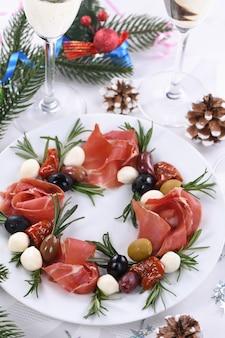 Ghirlanda di natale - antipasto. prosciutto di parma con olive, mozzarella baby e pomodori secchi