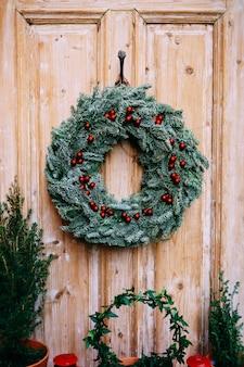 Ghirlanda di natale di rami di abete su una porta di legno. foto di alta qualità