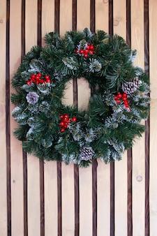 Ghirlanda di natale di aghi di pino, con bacche rosse invernali e coni su fondo in legno.