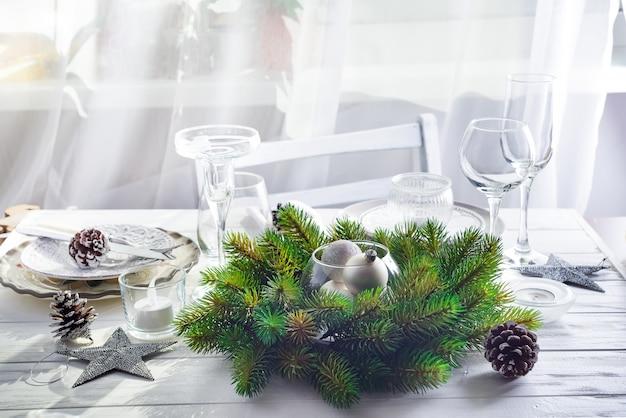 Ghirlanda di natale con i giocattoli sul tavolo con silver christmas table setting