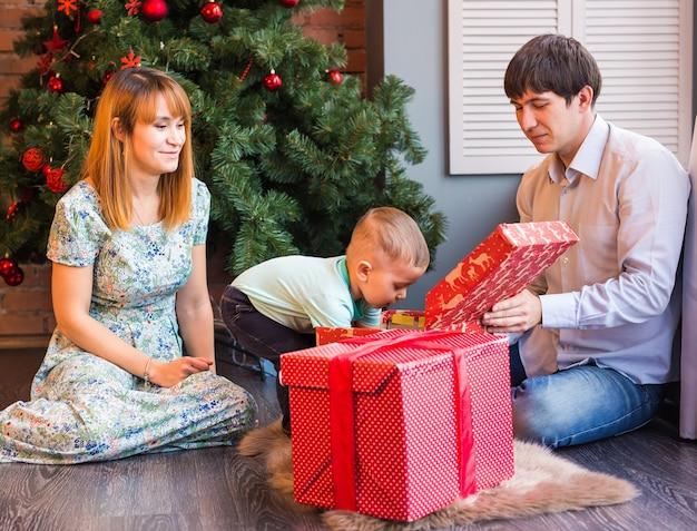Natale, natale, famiglia, persone, concetto di felicità - genitori felici che giocano con il neonato sveglio
