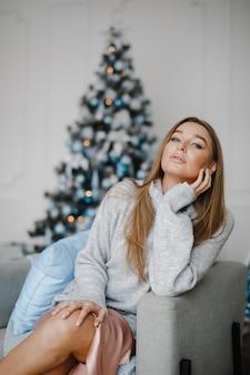 Natale, natale, inverno, concetto di felicità - donna sorridente con molte scatole regalo. la ragazza apre un regalo sullo sfondo dell'albero di natale. felice giovane donna che celebra il natale