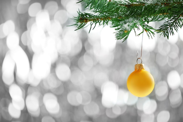 Pallina di natale gialla su un ramo di abete e superficie glitterata