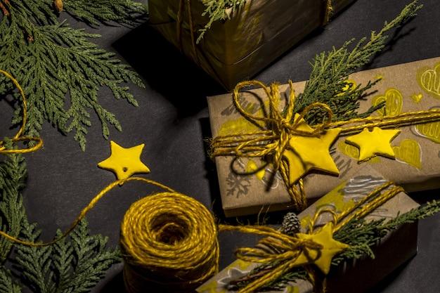 Contenitori di regalo fatti a mano gialli di natale sulla vista superiore del fondo nero. cornice di buon natale. tema per le vacanze invernali di natale. buon anno. disposizione piatta.