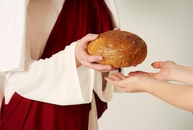 Le mani di cristo che consegnano la pagnotta di pane