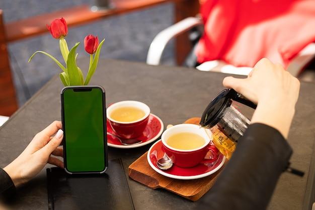 Schermo del telefono chroma key nelle mani della donna che beve il tè nella caffetteria con spazio copia, lifestyle