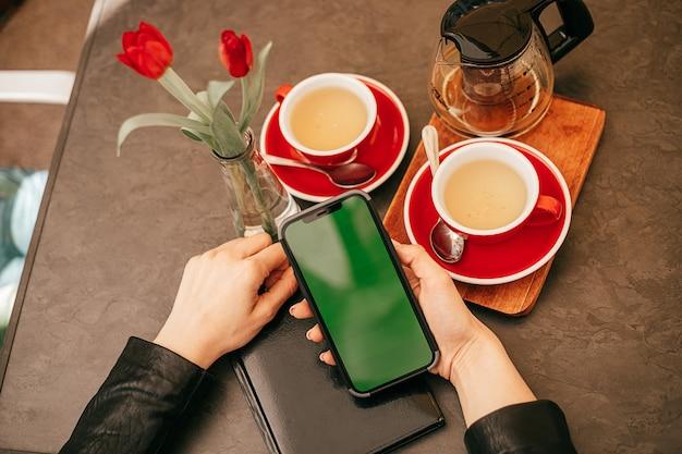 Schermo del telefono chroma key nelle mani di una donna che beve il tè in un bar con spazio per le copie