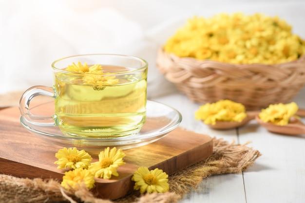 Tè del crisantemo e merce nel cestino del fiore del crisantemo su legno bianco