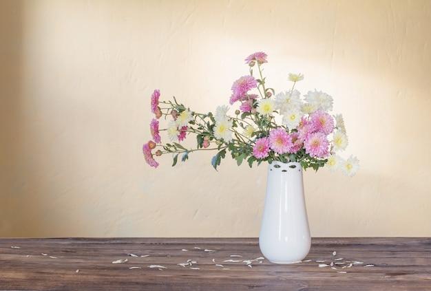 Crisantemi in vaso sul vecchio tavolo in legno