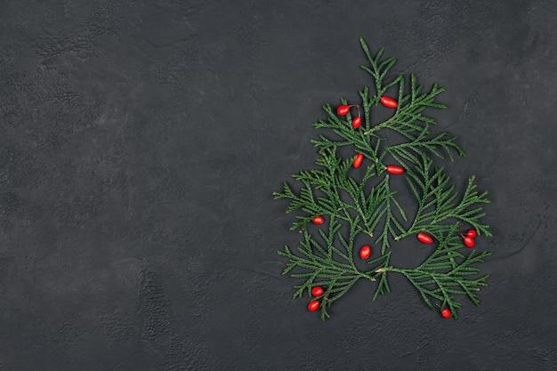 Chtristmas albero di ramoscelli verdi e bacche rosse su fondo nero
