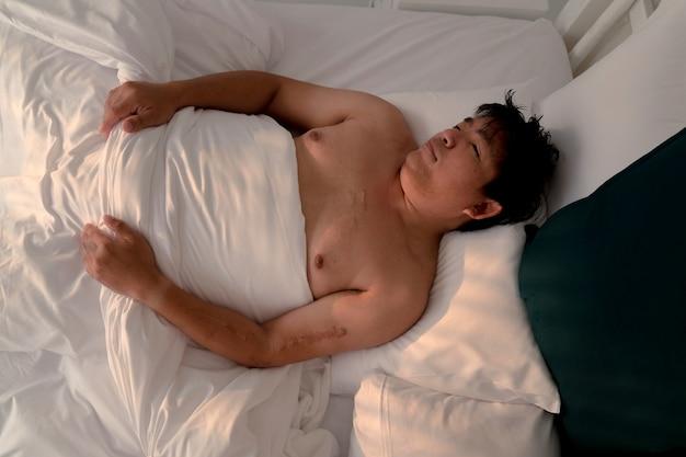 Uomo asiatico paffuto che dorme nel letto bianco con la faccia felice al mattino, bel sogno, giornata pigra