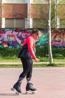 Ragazza bionda paffuta con occhiali pattinaggio a rotelle su un parco