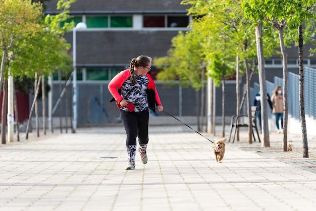 Ragazza bionda paffuta con gli occhiali che corre con il suo cane in una strada cittadina.