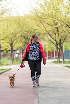 Ragazza bionda paffuta con gli occhiali che cammina con il suo cane nel parco.