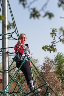La ragazza bionda paffuta con gli occhiali si è arrampicata sulla cima di una corda della piramide del parco giochi.