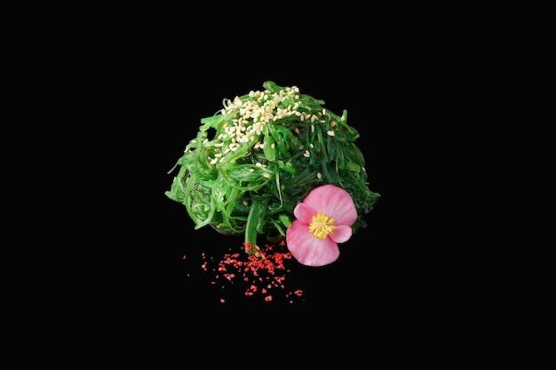 Insalata chuka con salsa di noci, semi di sesamo, erba cipollina, limone, microgreen isolato su fondo nero