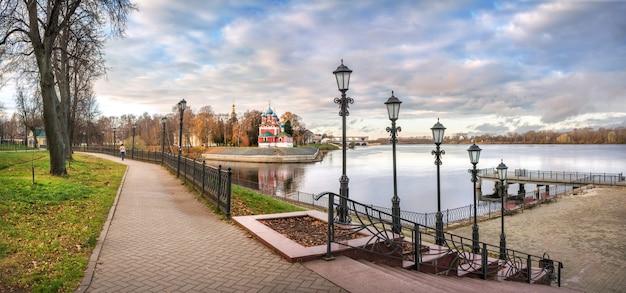 Chiesa di dmitry on blood a uglich sulle rive del fiume volga e un panorama dell'argine con lanterne sotto i raggi del sole autunnale