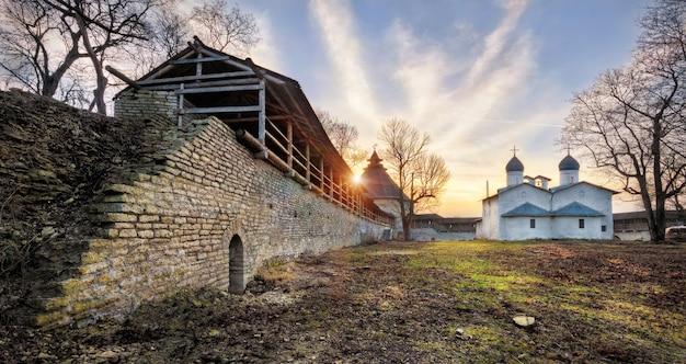 Chiesa dell'intercessione e della natività della vergine a pskov e il vecchio muro di mattoni del cremlino in una soleggiata sera d'autunno