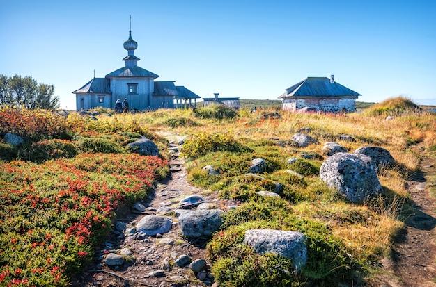 Chiesa di sant'andrea il primo chiamato sull'isola zayatsky e un sentiero di pietre ed erba in un paesaggio di tundra