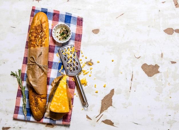 Ciabatta con formaggio e rosmarino sul tessuto. su fondo rustico. spazio libero per il testo. vista dall'alto