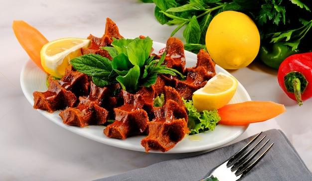 Cig kofte (polpetta cruda in turco) con lattuga, pomodoro, sottaceti e limone, chee kofta caldo. concetto di cibo crudo locale turco
