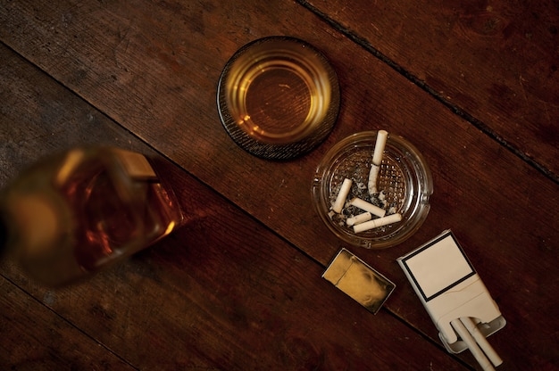 Sigaretta nel posacenere e bevanda alcolica in bottiglia sul tavolo di legno, vista dall'alto. cultura del fumo di tabacco, sapore specifico. concetto di cattive abitudini