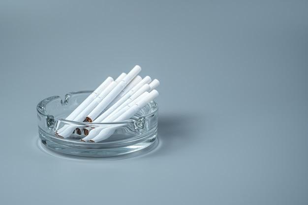 Una sigaretta in un portacenere su sfondo nero.