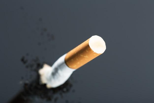 Mozzicone di sigaretta su grigio con riflesso