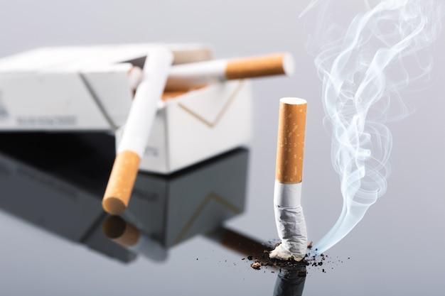 Mozzicone di sigaretta e pacchetto su grigio, foto in studio