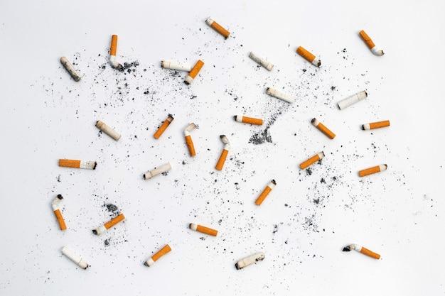 Mozziconi di sigaretta e ceneri su sfondo bianco.