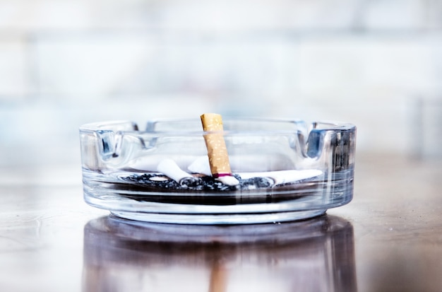 Mozziconi di sigaretta e posacenere in un bicchiere, smettete di fumare.