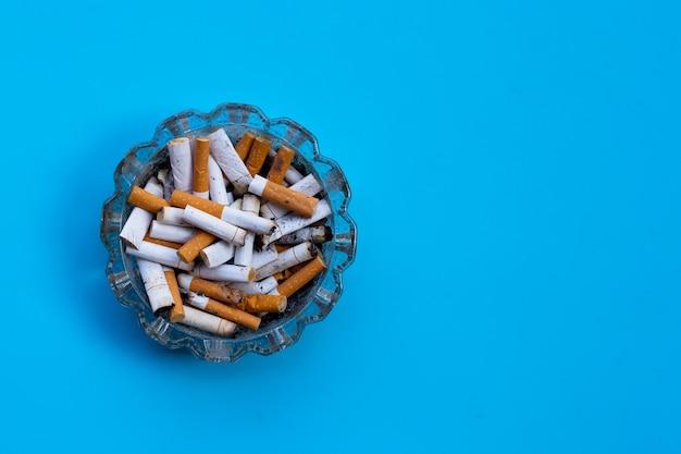 Mozziconi di sigaretta nel portacenere di vetro sulla superficie blu